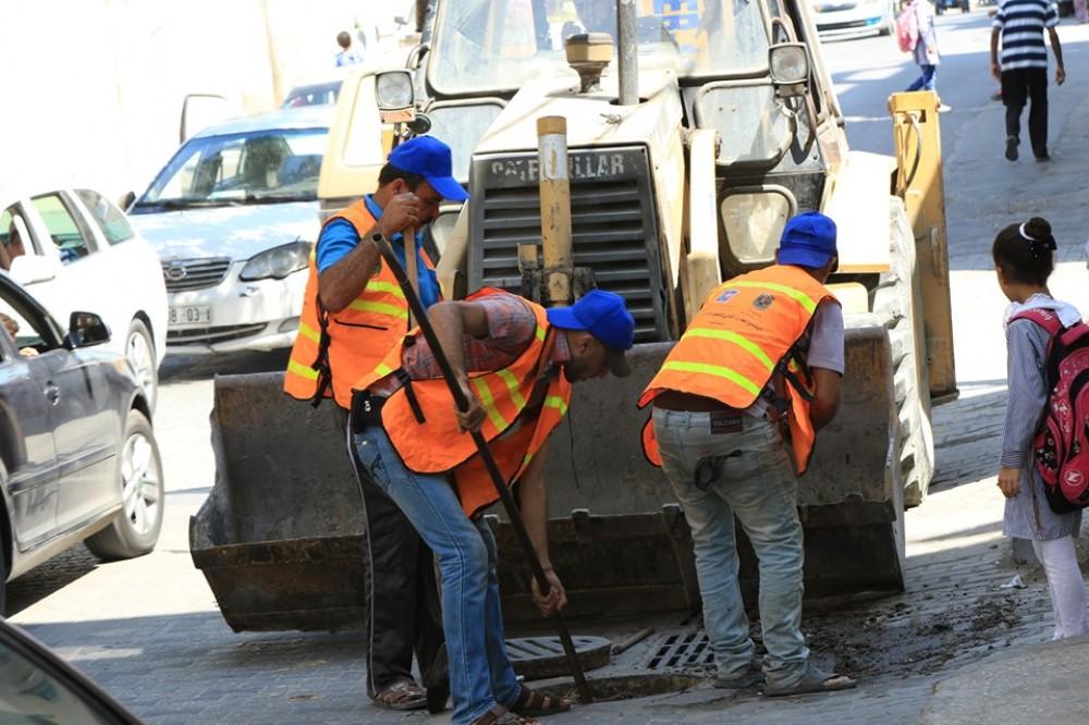 طواقم بلدية غزة خلال تنظيف مصارف المياه