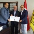 غازي بسيسو خلال توقيعه اتفاقية مع إبراهيم شجلر