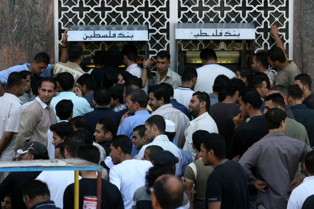 Palestinian-Authority-employees-line-up-in-front-of-a-bank-to-receive-their-salaries-after-four-days-of-delaying