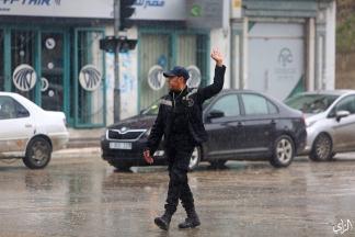 تحت الأمطار.. أحد عناصر شرطة المرور يضبط الحركة المرورية في مدينة غزة . تصوير: عطية درويش
